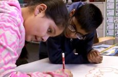 Two young students drawing on a poster.