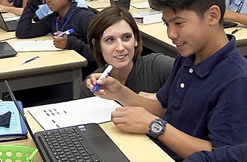 Teacher with student working on online Khan Academy exercises on computer.
