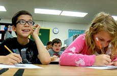 Two young students with autism writing at their desk.