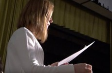 Female student looking down at paper while rehearsing her debate speech.