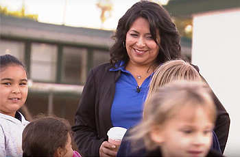 School principal, Roxanna Villasenor talking with students on playground.
