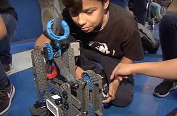 Male student kneeling down working on his robot.