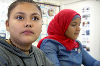 Two female refugee students sitting in classroom.