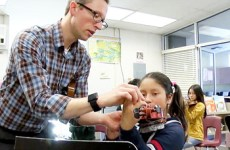 teacher helping student place fingers on violin