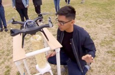 student kneeling looking at drone