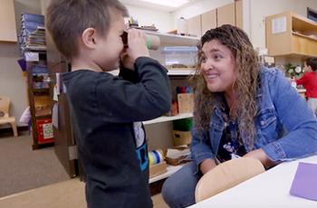 a preschooler looks through make-believe binoculars at teacher