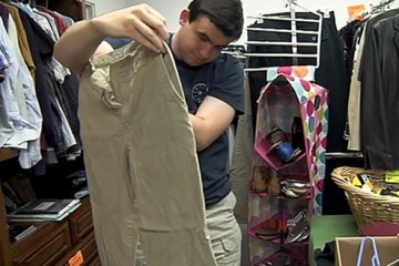 student holding up pants at thrift store