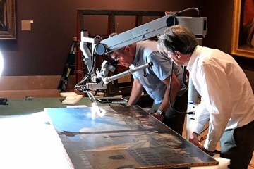 museum curators looking at a painting