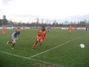 Croydon defender Oliver Hunt, in orange, tries to get away from Darren Blake, Badshot Lea's outstanding winger