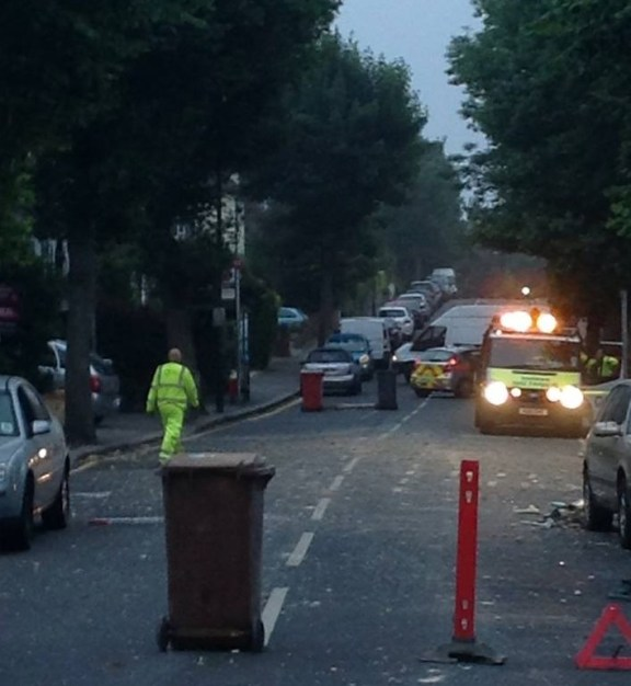 "With police and the council emergency ""team"" on the scene, Mayfield Road has a makeshift roadblock, comprising the brown Southwark wheelie bin full of builders' rubble"