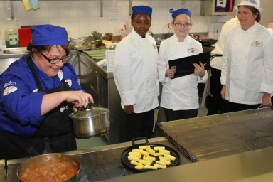 St Giles school chef Sharon Taylor, in blue, hard at work in the school dinners competition at Croydon College, watched over by the judges, including two pupils from Whitehorse Manor,