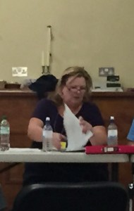 Elizabeth Ash, as seen from towards the back of a not very full hall, struggling with her paperwork as she presides over the meeting