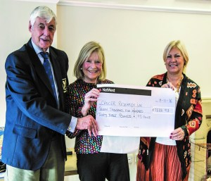 John Collins, former WRFC chairman now president of Surrey RFU, hands over the charity donation for Cancer Research