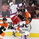 NHL 2015 - Sept 22 - NYR vs PHI - Center Luke Adam (#17) of the New York Rangers knocks Defenseman Shayne Gostisbehere (#53) of the Philadelphia Flyers off of his skates