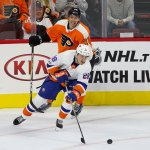 Defenseman Sebastian Aho (#28) of the New York Islanders plays the puck away from Left Wing Isaac Ratcliffe (#76) of the Philadelphia Flyers