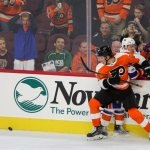Center Nolan Patrick (#64) of the Philadelphia Flyers and Center Scott Eansor (#36) of the New York Islanders collide along the boards
