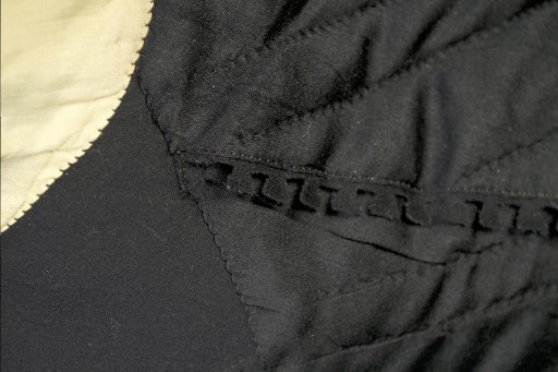 The raw edge of the lining has been finished with elaborate dovetail like pattern.