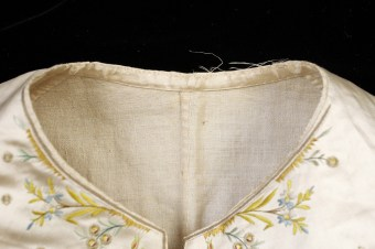 The edges of the waistcoat along the neck are finished with a facing of silk satin, but the back of the piece is made from a coarse linen. The seam along the center back is felled although the hand stitching is relatively widely spaced.