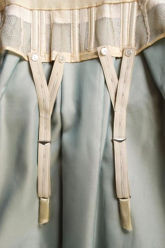 The dress includes suspenders for the garters that are attached to the dress with buttons. the elastic straps have multiple buttonholes so the length of the suspenders could be adjusted.