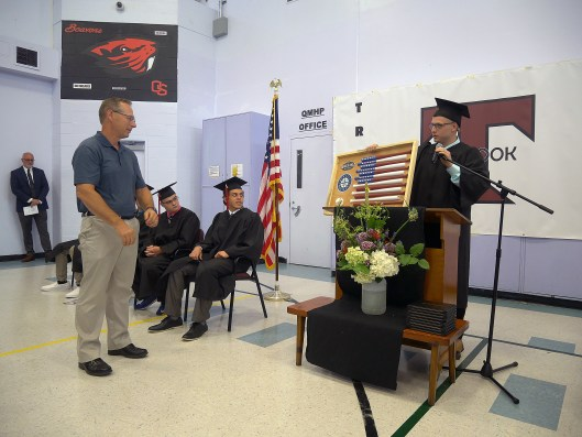 Eric Y. presents Randy Schild, retiring Tillamook School District superintendent, with a gift made in the Trask River High School's woodshop during the school's graduation ceremony.