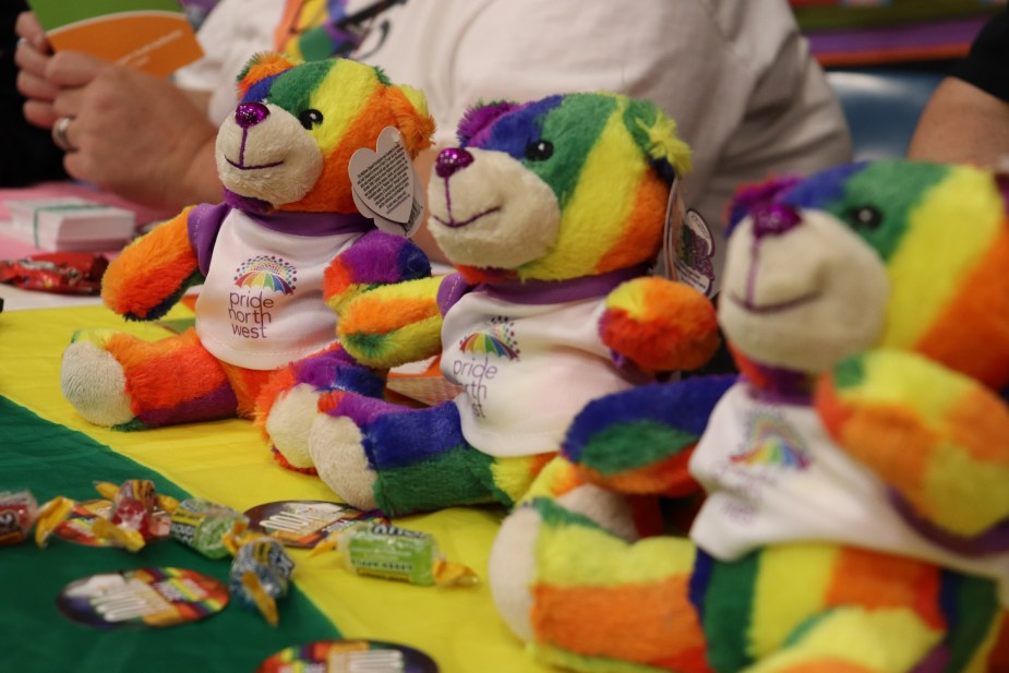 Multi-colored Pride teddy bears lined up on table.
