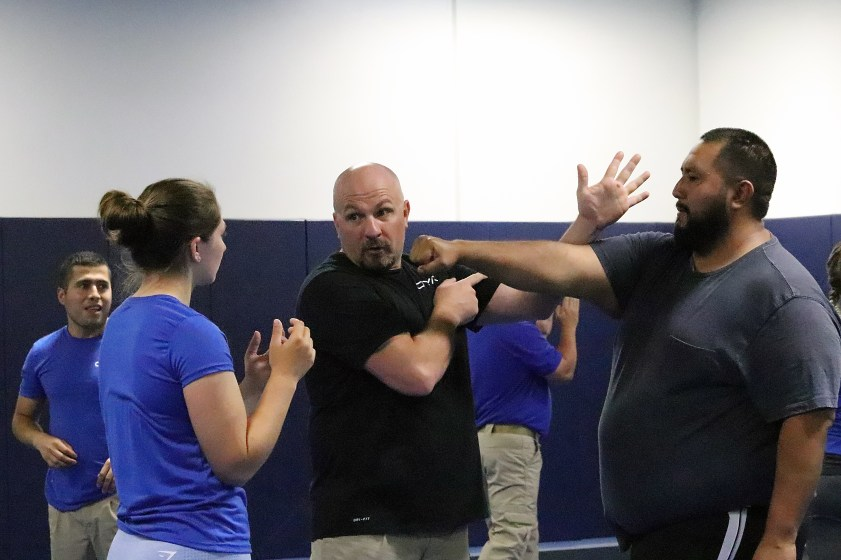 Trainer Caleb Bronemann demonstrates a self-defense move to a new group life coordinator during New Employee Orientation at the OYA Training Academy.