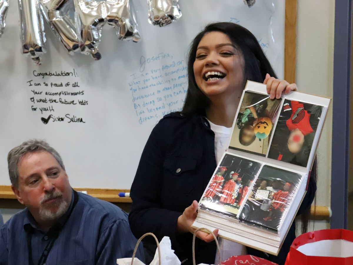 Josefina holds up photo album at party