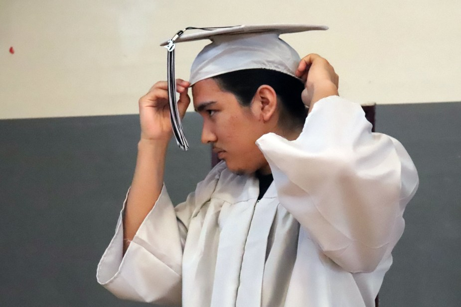 student puts on graduation cap