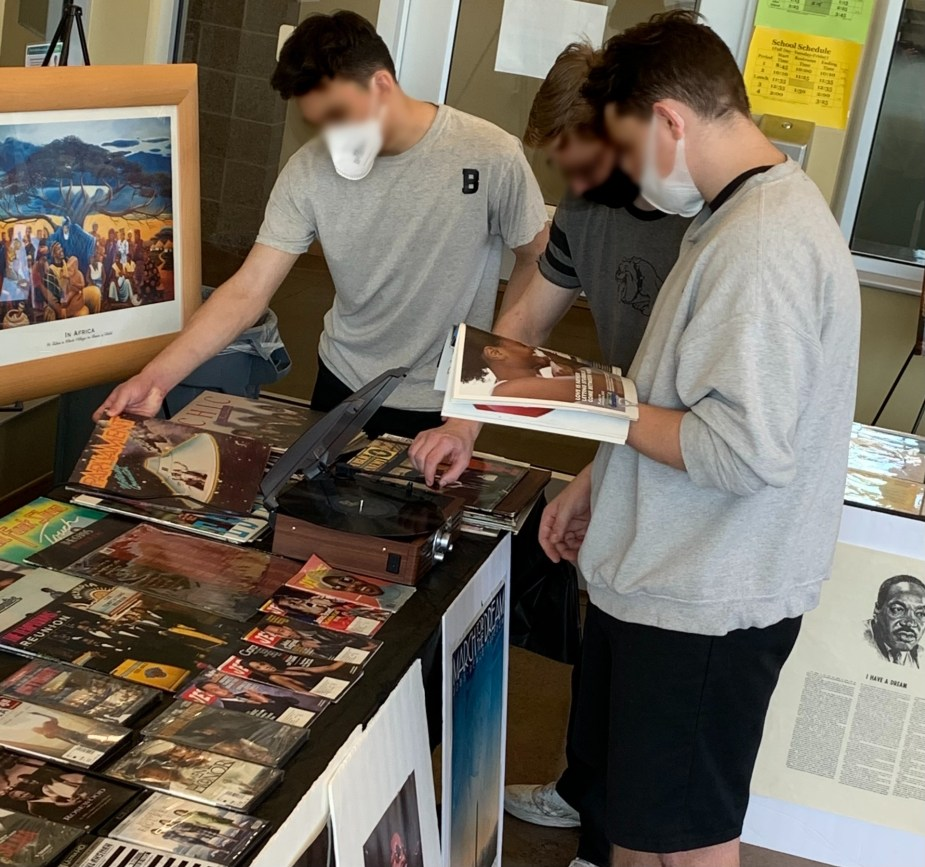 Three young men look at pictures from the museum laid out on a table.