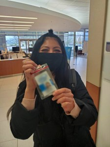 young woman holding ID badge and smiling from behind face covering