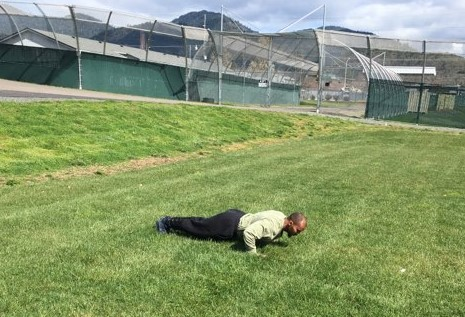 a young man does pushups outside in a grassy field