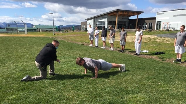 a man kneels next to a teenager doing pushups in a field outside