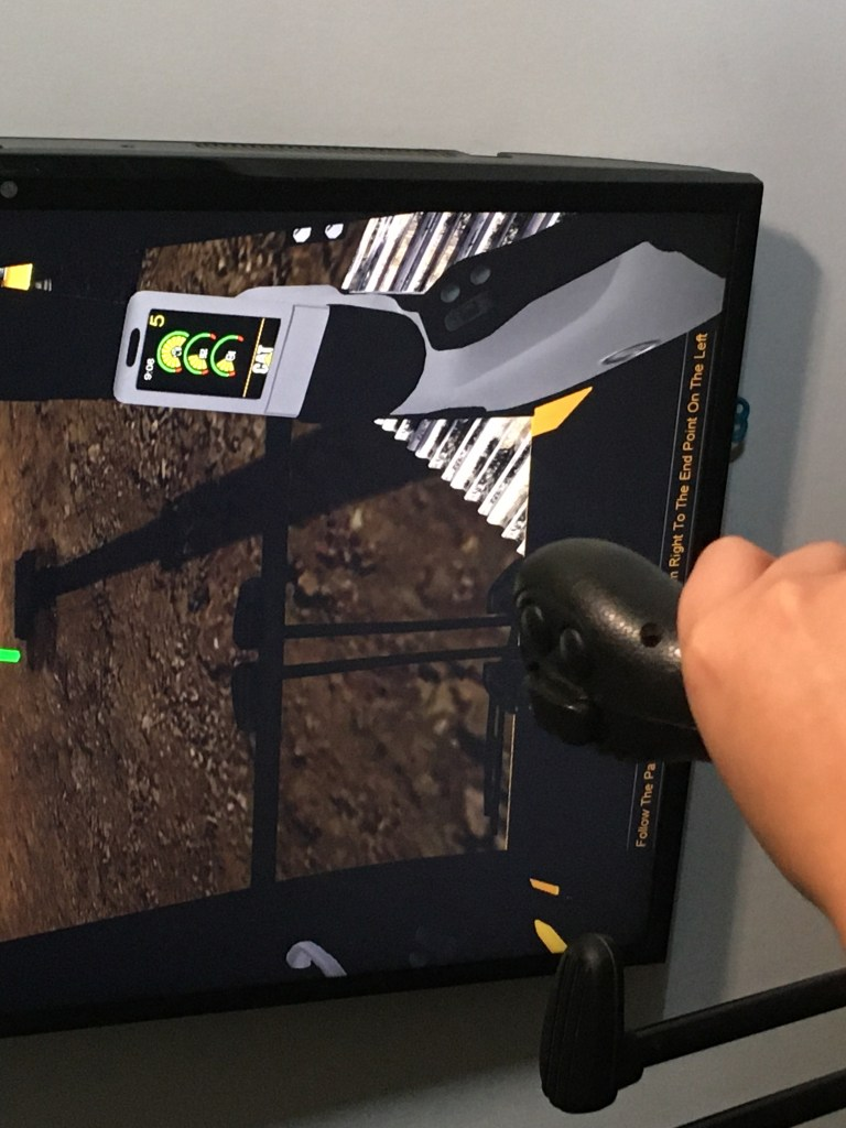 a hand using a joystick in front of a screen