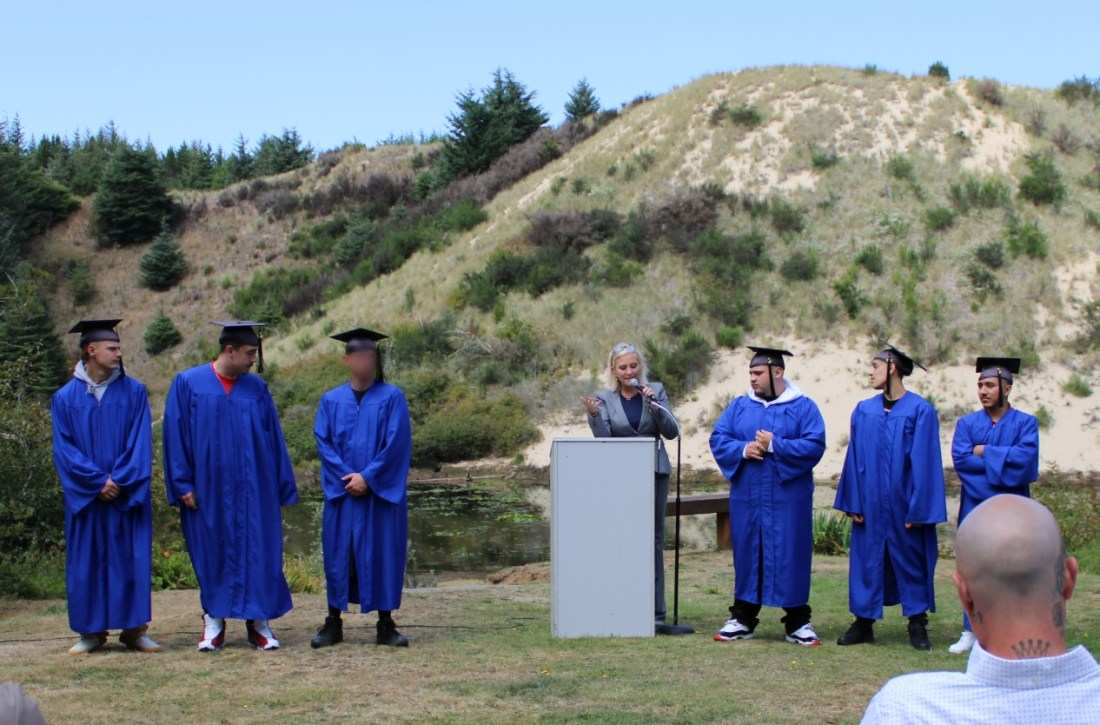 three graduates in blue cap and gown standing outside with principal at a podium