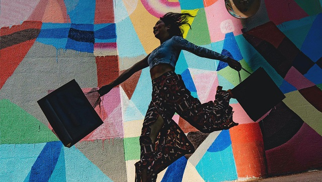 Image of woman jumping with shopping bags against colourful mural.
