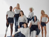 A group of diverse women with white tops and jeans on.