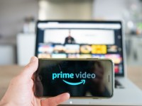 a picture of someone holding a video with prime video on the screen