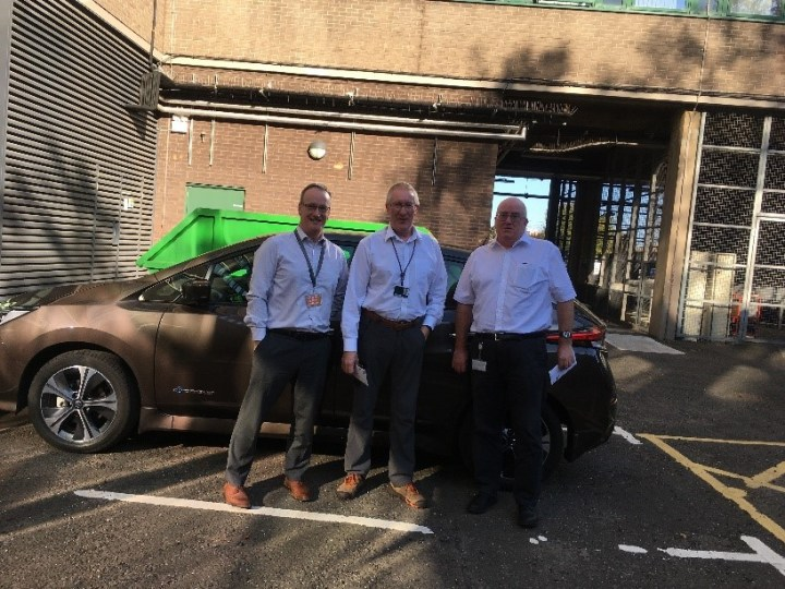 Three members of staff stand in front of Nissan Leaf electric car