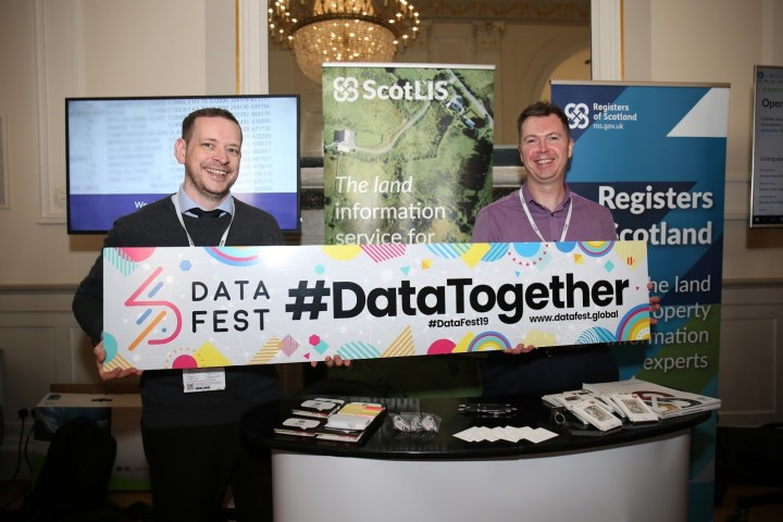 Two members of RoS staff holding at '#DataTogether' banner at DataFest 2019