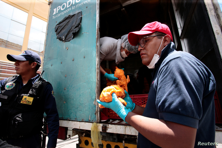 People stand in line to receive chicken as roadblocks have caused a food and fuel crisis, in La Paz, Bolivia, Nov. 18, 2019.
