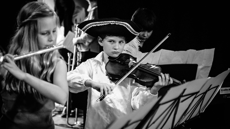 In the center of a black-and-white photo, a boy wearing a three-cornered hat playing a violin looks unfavorably towards an slightly out-of-focus blonde girl playing the flute to his right.