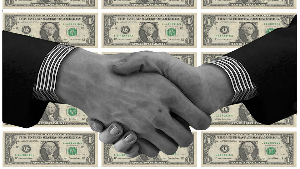 Two identical hands shaking. Identical, striped cuffs. The hand on the left has a mole at the bottom of the third finger. $1 bills are in the background. The photo is black-and-white.