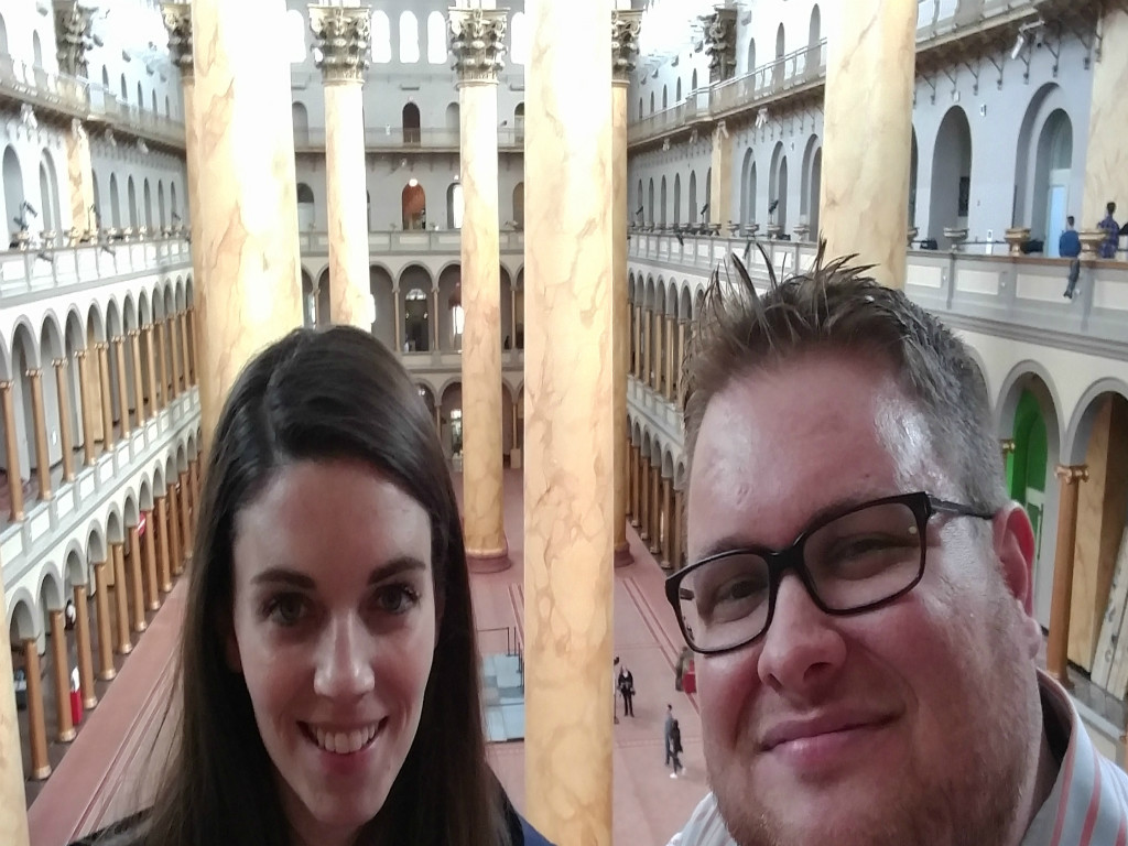 Brown-haired woman on the left, smiling. Blond-haired man with dark thick-framed glasses to the right, smiling. Behind them is the interior of the National Building Museum. They are standing on the third floor. The room is sunlit and there are beige, marble pillars.