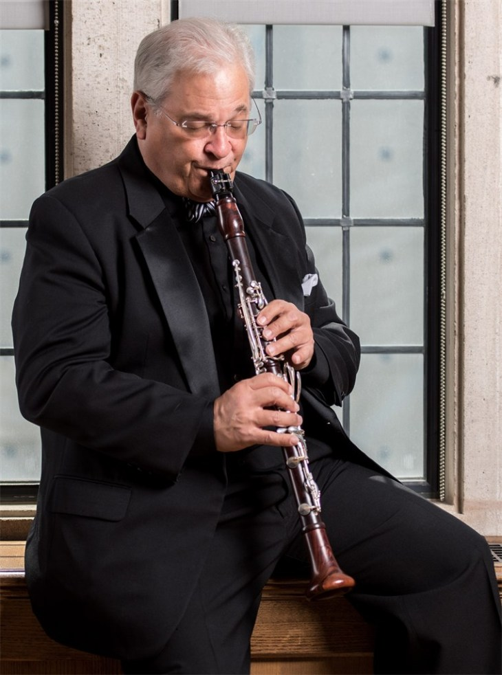 David Shifrin sitting on a table in a black tuxedo playing the clarinet