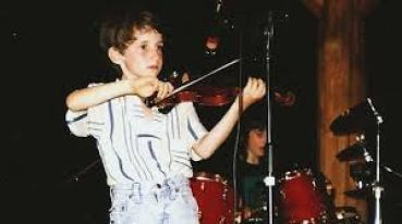 Noah Bendix-Balgley playing his violin as a child.