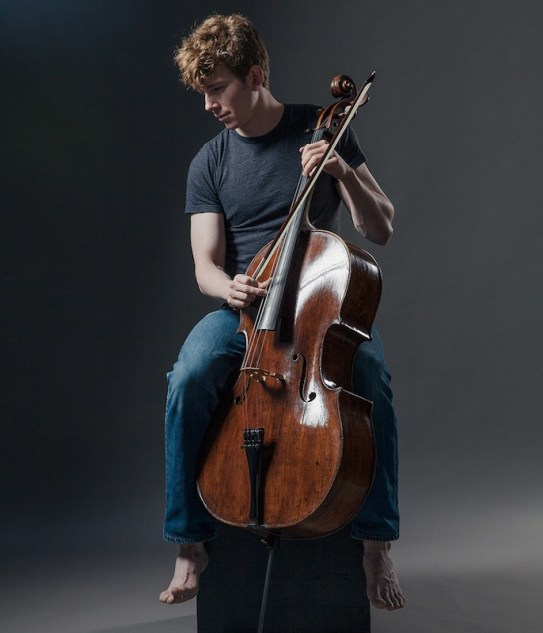 Joshua Roman sitting in a studio bare footed holding his cello