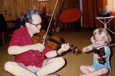3 year old Kimberly Fisher sitting cross legged with her father playing violin.