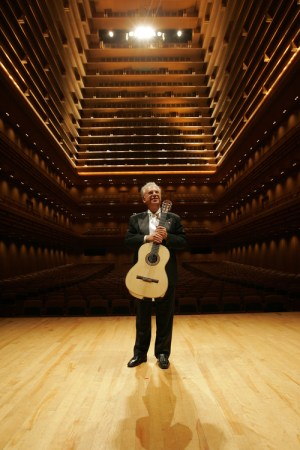Pepe Romero standing on the stage in a beautiful empty hall with his back to the seats