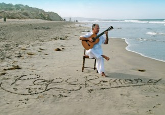 Pepe Romero sitting on the beach with guitar in hand and name written in the sand.