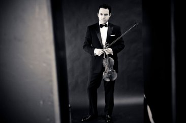 black and white vintage picture of Giora Schmidt posing in a tux holding his violin.